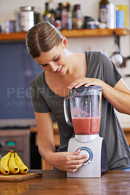 Buy stock photo Shot of an attractive young woman preparing a fruit smoothie