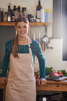 Buy stock photo Portrait of an attractive young woman wearing an apron standing in the kitchen