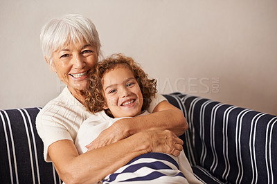 Buy stock photo Shot of a grandmother embracing her grandson while they sit on the sofa