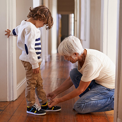Buy stock photo Shot of a grandmother tying her grandson's shoelaces for him