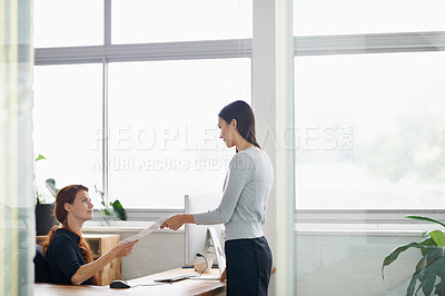 Buy stock photo Shot of a young businesswoman handing her colleague a document