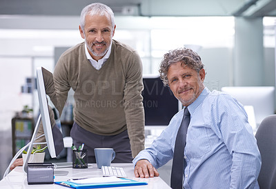 Buy stock photo A mature businessman sitting at his workstation with his colleague standing by