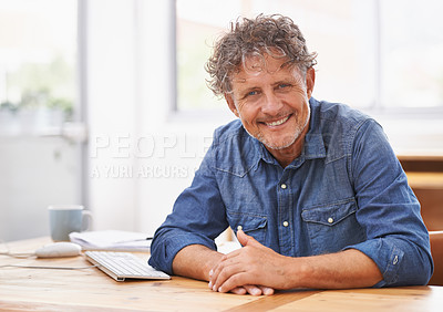 Buy stock photo Shot of a mature businessman sitting at his office desk