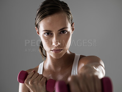Buy stock photo Cropped shot of a woman punching while holding dumbells