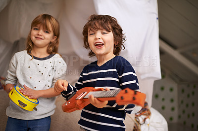 Buy stock photo Portrait of two adorable siblings playing with their musical toys