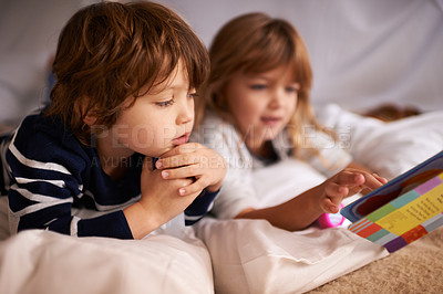 Buy stock photo Shot of two adorable siblings using torches to read a book inside their blanket fort