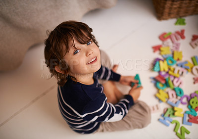 Buy stock photo Portrait of an adorable little boy playing with colorful toy letters