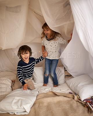 Buy stock photo Shot of two adorable siblings jumping on the mattress underneath their fort