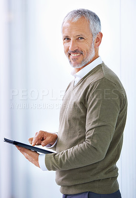 Buy stock photo Portrait of a mature businessman standing with his digital tablet at the office