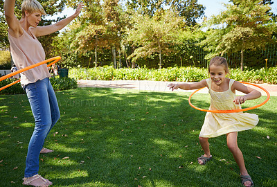 Buy stock photo A happy young mother and daughter hula hooping in the park on a sunny day