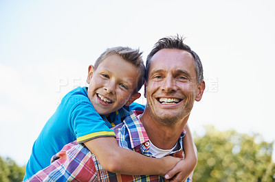 Buy stock photo A cropped portrait of a happy father giving his young son a piggyback ride