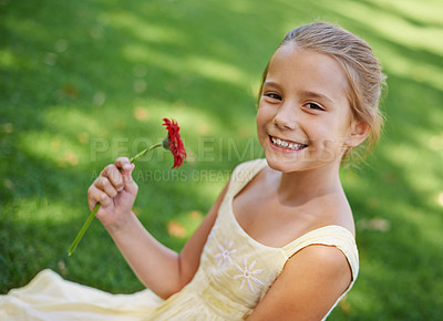 Buy stock photo A portrait of a beautiful little girl holding sitting outside on the grass with a beautiful red flower