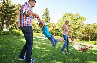 Buy stock photo Two parents swinging their young children around as they play in the park on a beautiful sunny day