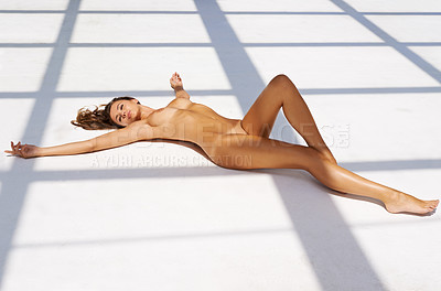 Buy stock photo A beautiful nude woman lying on a sunlight white floor