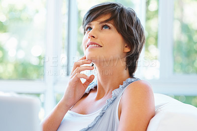 Buy stock photo Pretty young woman with hand on face looking into distance