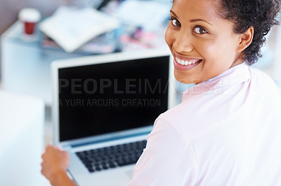 Buy stock photo A woman smiling over her shoulder at youwhile using her laptop - copyspace