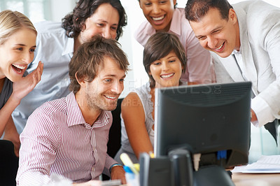 Buy stock photo Successful business team smiling and looking at the computer