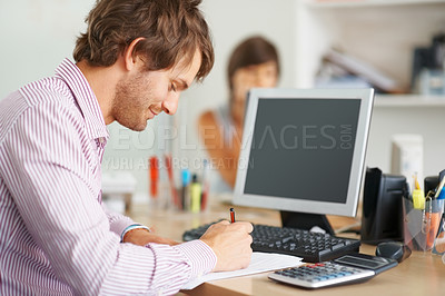 Buy stock photo Young business man calculating budget using calculator at office