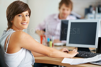 Buy stock photo Young business woman working on computer and looking at you