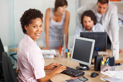 Buy stock photo Young business woman working on computer with her team in background