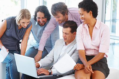 Buy stock photo Young business people working together on laptop