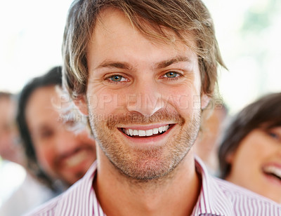Buy stock photo Handsome young guy with team in background