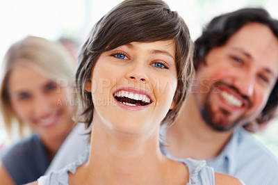 Buy stock photo Attractive young woman laughing with blur team in background