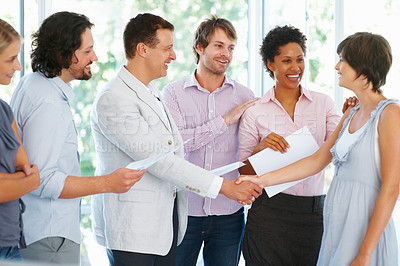 Buy stock photo Business man shaking hands with female executive while team looking at her