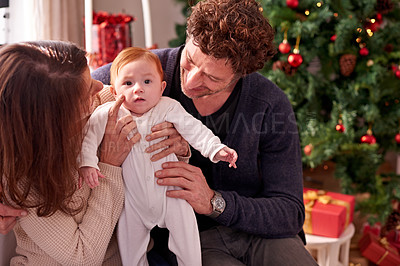 Buy stock photo Cropped shot of an affectionate couple with their baby on Christmas morning