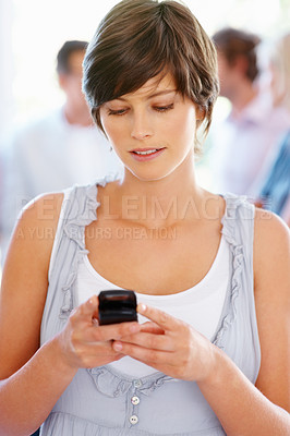 Buy stock photo Pretty woman texting message with blur people in background
