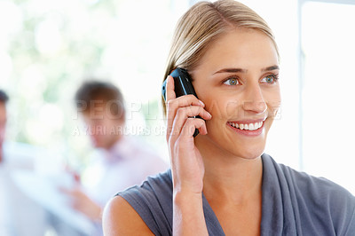 Buy stock photo Pretty woman talking on cell phone with team in background