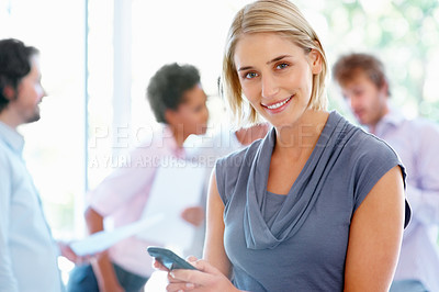 Buy stock photo Young business woman holding cell phone with colleagues in background