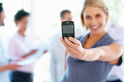 Buy stock photo Happy business woman displaying cell phone with team in background