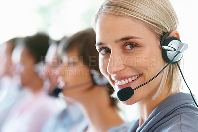 Buy stock photo Pretty female executive wearing headset with colleagues in background