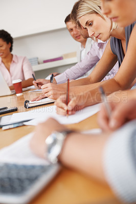 Buy stock photo Business people taking notes during meeting
