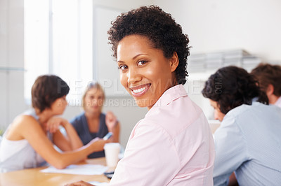 Buy stock photo African American woman smiling with team discussing in background
