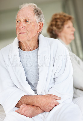 Buy stock photo Closeup shot of an unhappy senior man with his wife sitting in the background