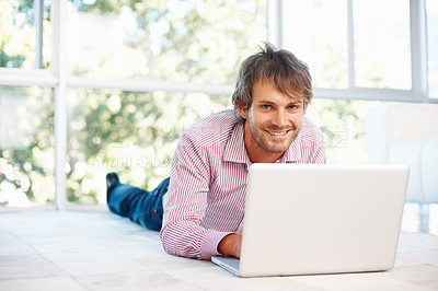 Buy stock photo Smiling young man working on laptop while lying on floor