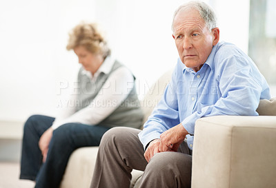 Buy stock photo A senior couple sitting on opposite ends of the sofa after an argument