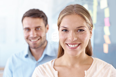 Buy stock photo Portrait of two positive-looking young business professionals standing in an office