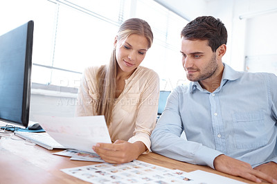 Buy stock photo Shot of two young designers sitting at a table and editing photographs