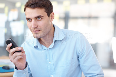Buy stock photo Shot of a handsome young business professional sending a text on a mobile phone