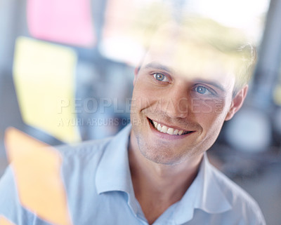 Buy stock photo Through the glass shot of a young businessman looking at sticky notes on a glass wall