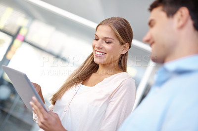 Buy stock photo Low angle shot of two young business professionals working on a digital tablet