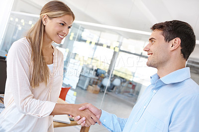 Buy stock photo Shot of two young business professionals shaking hands in the office