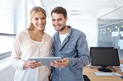Buy stock photo Two young businesspeople holding a digital tablet while smiling at the camera - copyspace