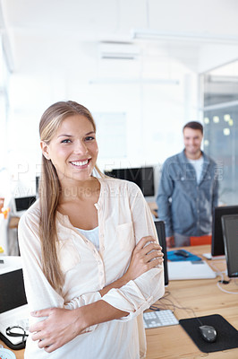 Buy stock photo Lovely young businesswoman smiling at the camera while her male colleague stands in the background - portrait