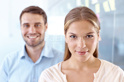 Buy stock photo Young businesswoman looking at the camera with her male colleague standing behind her