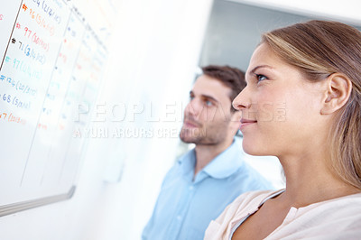 Buy stock photo Two businesspeople looking at figures written on a whiteboard - copyspace