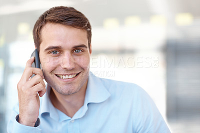 Buy stock photo Handsome young businessman smiling at the camera while holding a cellphone - copyspace